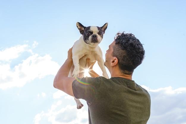 Unerkennbarer mann, der eine bulldogge hält horizontale ansicht des mannes mit haustier im freien. lebensstil mit tieren