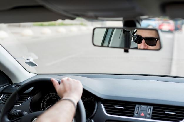 Unerkennbarer mann, der in auto auf verkehrsreiche straße reitet