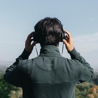 Unerkennbarer mann, der musik hört