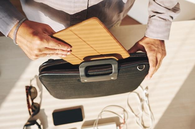 Unerkennbarer mann, der tablet-computer in aktenkoffer setzt