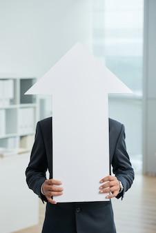 Unerkennbarer mann in der klage, die im büro steht und den großen weißen pfeil aufwärts zeigt hält