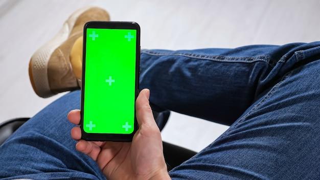 Unerkennbarer mann sitzt mit über dem knie gekreuzten beinen auf einem stuhl und hält ein telefon mit grünem bildschirm in den händen