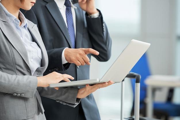 Unerkennbarer mann und frau in den anzügen, die zusammen laptopschirm betrachten
