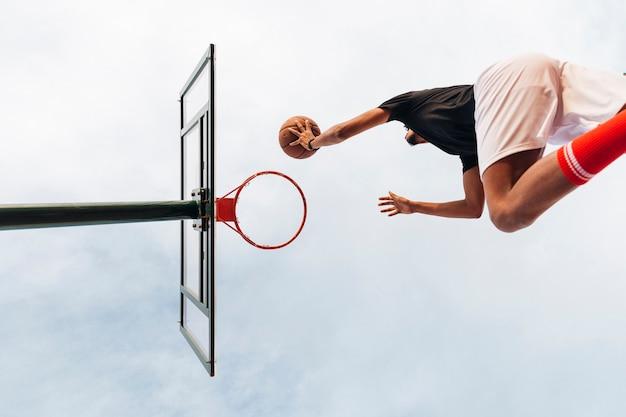 Unerkennbarer sportlicher mann, der basketball in netz wirft