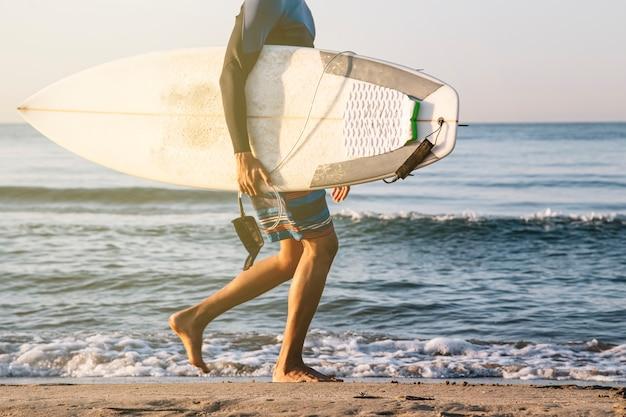 Unerkennbarer surfer, der mit surfbrettern am strand entlang läuft