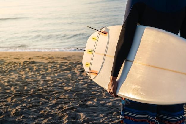 Unerkennbarer surfer mit surfbrett, das im licht des sonnenaufgangs am strand entlang läuft