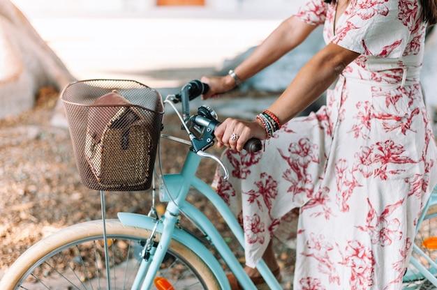 Unerkennbares junges mädchen in der stadt mit retro-fahrrad