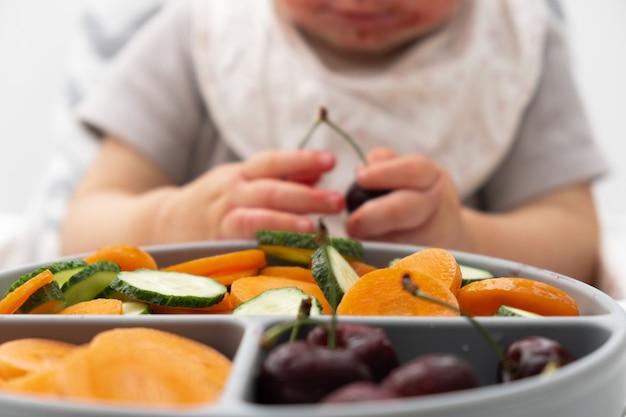 Unerkennbares kaukasisches baby etwa 1 jahr alt, das von einem silikonteller mit frischem gemüse obst beeren isst