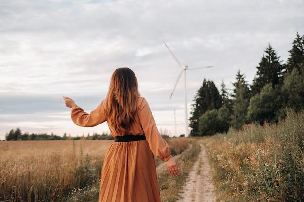 Unerkennbares mädchen in einem orangelangen kleid mit langen haaren in der natur am abend vor dem hintergrund eines waldes und einer windmühle.europa