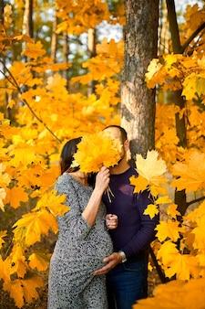 Unerkennbares paar, schwangere frau und ihr ehemann, die den bauch in der natur umarmen, im wald zwischen herbstblättern stehen, fallen. neues lebenskonzept.