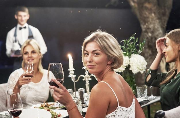 Unerwartete porträtansicht. eine gruppe erwachsener freunde ruht sich abends im hinterhof des restaurants aus und unterhält sich.