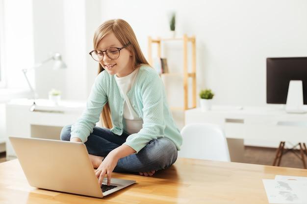 Unerwartete pose. engagiertes verantwortungsbewusstes kluges mädchen, das auf dem tisch sitzt und ihren laptop benutzt