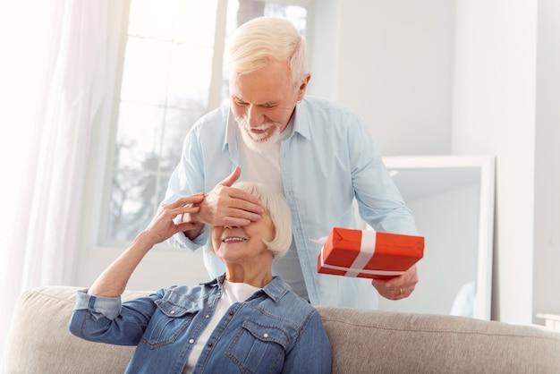 Unerwartete überraschung. glücklicher älterer mann, der eine geburtstagsüberraschung für seine geliebte frau macht, ihre augen mit einer hand bedeckt und ihr ein geschenk gibt