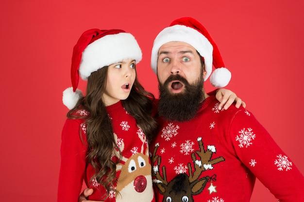 Unerwartete überraschung. weihnachtszeit. neujahrsparty. glücklich, zusammen zu sein. winterurlaub mit der familie. glücklicher vater und tochter lieben weihnachten. kleines mädchen und papa weihnachtsmütze. papa und kind roter hintergrund.