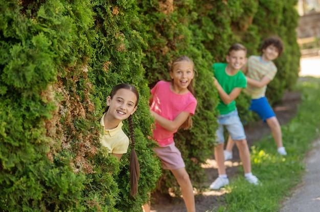 Unerwarteter moment. begeisterte lächelnde mädchen und jungen, die an einem sommertag aus den büschen im park springen
