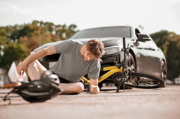 Unfall auf der straße. dunkelhaariger mann mit schlechtem gefühl in sportkleidung, der auf der straße vor einem schwarzen auto vom fahrrad fällt