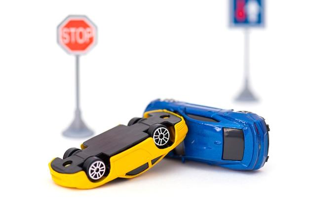 Unfall mit zwei spielzeugautos und schildstopp isoliert auf weiß. konzeptbild über unfall auf der straße
