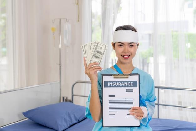Unfallpatientin verletzungsfrau auf patientenbett im krankenhaus, die uns dollarnoten hält, freut sich über versicherungsgeld von versicherungsunternehmen - medizinisches konzept