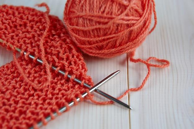 Unfertige arbeit handstricken aus roten wollfäden auf einem hölzernen hintergrund