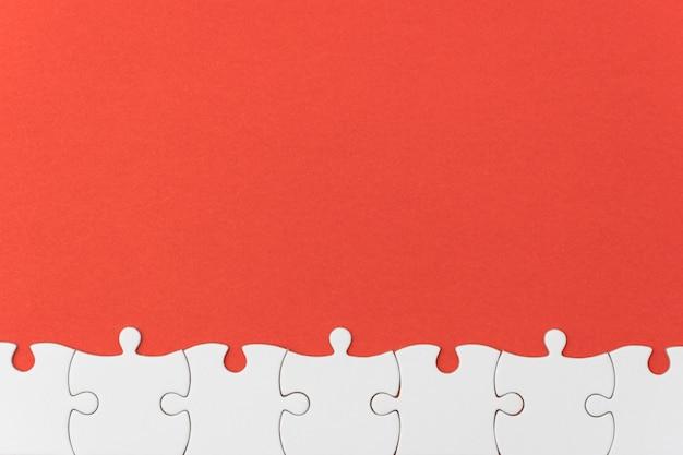 Unfertige puzzlebeschaffenheit auf rotem hintergrund.