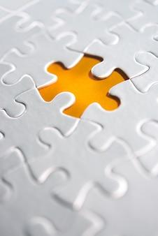 Unfertige weiße puzzlespielstücke auf orange hintergrund