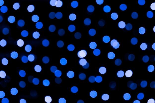 Unfocused abstrakter bunter bokeh schwarzhintergrund. unscharf gestellt und verschwommen viele runde blaue licht
