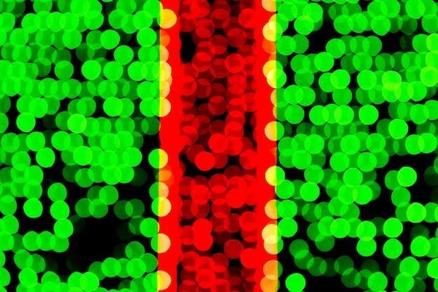 Unfocused abstraktes grünes und rotes bokeh auf schwarzem hintergrund.
