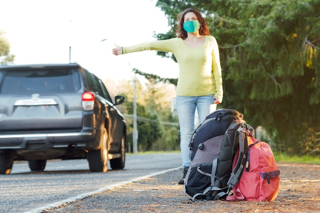 Unfokussierte frau, die eine schützende gesichtsmaske trägt, die auf einer landstraße per anhalter fährt.