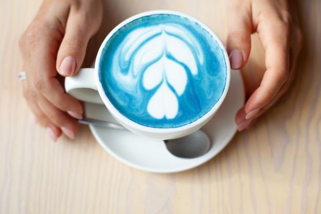 Unfokussierte frauenhände halten tasse heißen schmetterlingserbsenlatte oder blauen spirulina latte auf holztisch. bio gesundes und trendiges getränk. konzept für wohlbefinden und entgiftung. speicherplatz kopieren.
