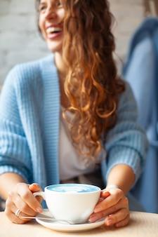 Unfokussierte glückliche frau mit langen gewellten haaren im warmen pullover, der tasse heißen blauen latte hält. trendiges getränk und farbe. blauer tee latte wird mit schmetterlingserbsenblüten hergestellt. gesundes kräutergetränk