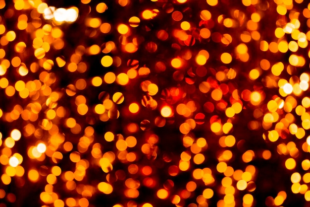 Unfokussiertes abstraktes orange bokeh auf schwarzem hintergrund. defokussiert und viele runde lichter verschwommen