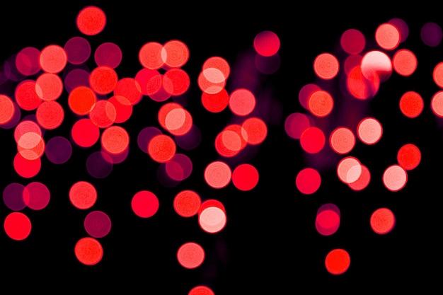 Unfokussiertes abstraktes rotes bokeh auf schwarzem hintergrund. defokussiert und viele runde licht verschwommen.