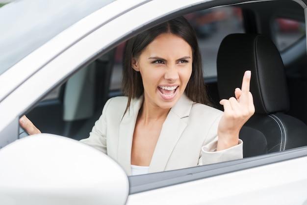 Unfreundlicher fahrer. wütende junge frau, die beim autofahren schreit und gestikuliert