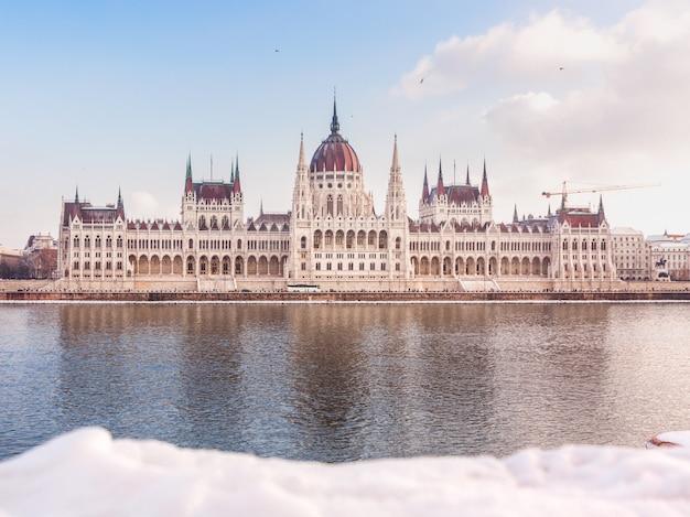 Ungarisches parlamentsgebäude am winter. schnee liegt am ufer des flusses, budapest, ungarn