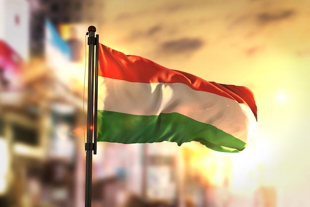 Ungarn flagge gegen stadt verschwommen hintergrund bei sonnenaufgang hintergrundbeleuchtung