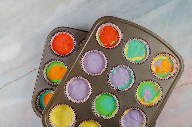 Ungebackene regenbogen-cupcakes auf zwei backblechen. ansicht von oben.