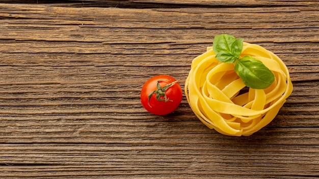 Ungekochte bandnudeln mit basilikumblättern und tomaten