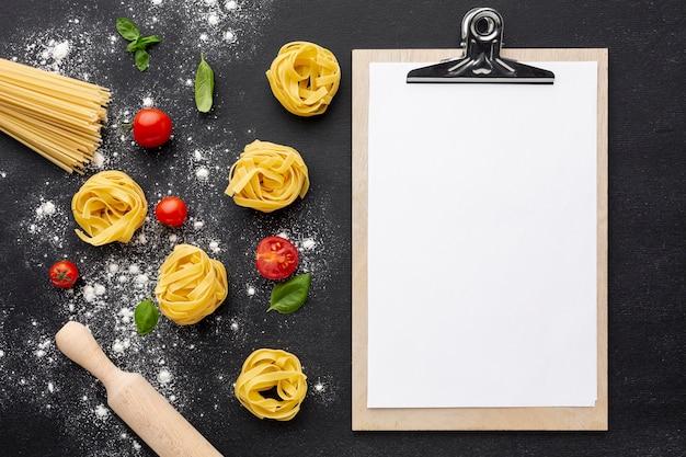 Ungekochte bandnudelspaghettis auf schwarzem hintergrund mit tomatennudelholz und klemmbrettmodell