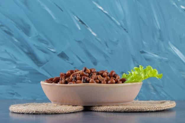 Ungekochte bohnen mit salat in einer schüssel auf untersetzer auf der marmoroberfläche