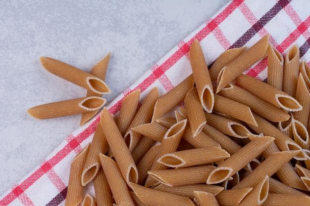 Ungekochte braune penne-nudeln auf gestreifter tischdecke