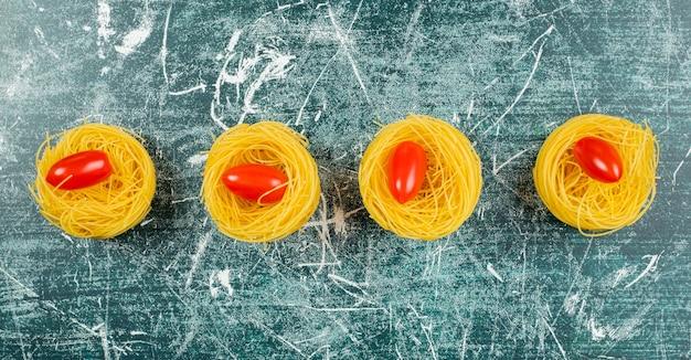 Ungekochte capellini-nudeln und tomaten, auf dem blau.