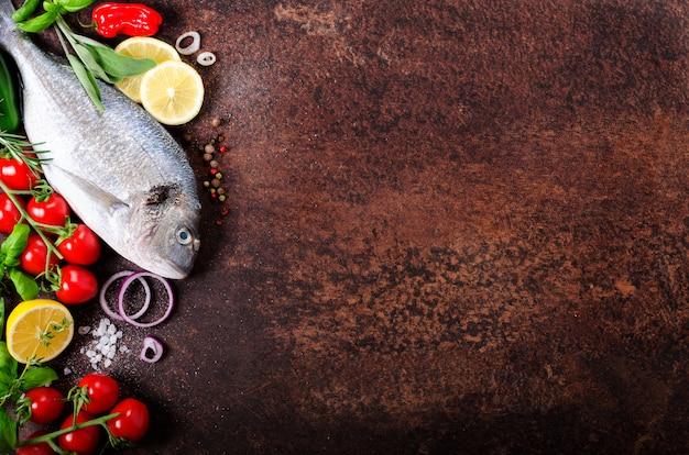 Ungekochte fische auf dunklem weinlesehintergrund.