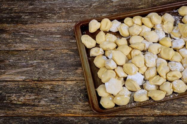 Ungekochte fleischknödel ravioli pelmeni auf altem holztisch