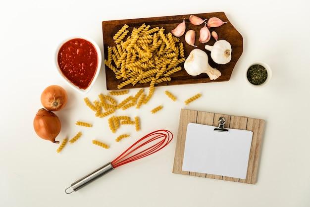 Ungekochte fusilli-nudeln und gesunde zutaten für die herstellung von nudeln