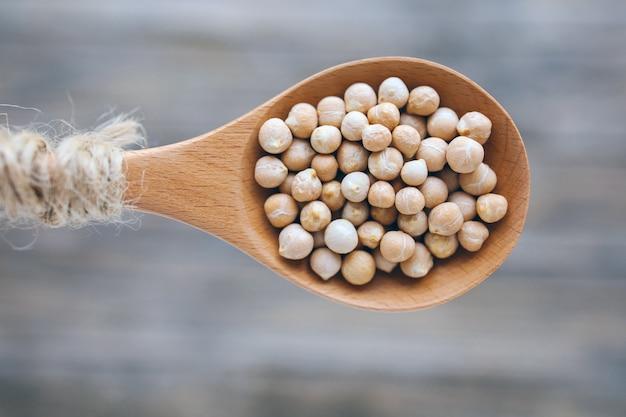 Ungekochte getrocknete hülsenfruchtkichererbsen oder kichererbsen in rustikalem holzlöffel auf unscharfem hintergrundve...