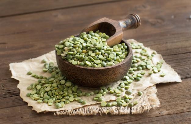 Ungekochte grüne erbsen in einer schüssel mit einem löffel auf einem holztisch