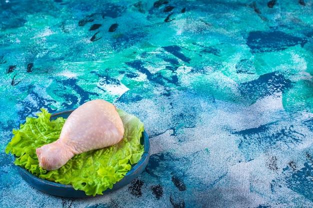 Ungekochte hähnchenkeule auf einem salat in einem teller