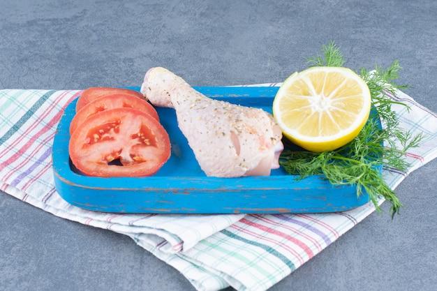 Ungekochte hähnchenkeule, tomaten- und zitronenscheibe auf blauem teller.