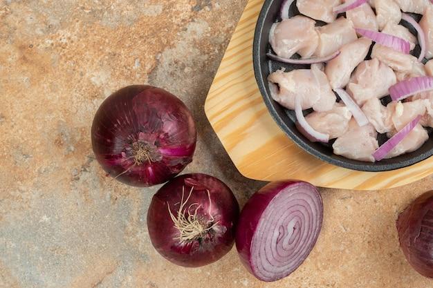 Ungekochte hähnchenschenkel in dunkler pfanne mit geschnittenen zwiebeln.