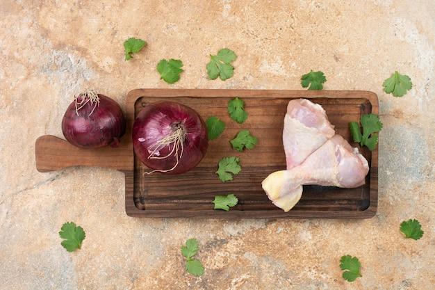 Ungekochte hähnchenschenkel in holzschneidebrett mit geschnittenen zwiebeln.